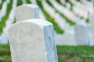 lápidas en un cementerio pacífico, enfoque selectivo en una piedra frontal. foto