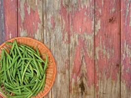 Green beans on a wicker plate on a wooden table background