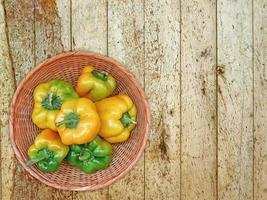 Pimientos verdes y amarillos en un plato de mimbre sobre un fondo de mesa de madera foto