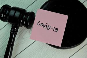 Covid-19 written on a notepad with gavel isolated on wooden table photo