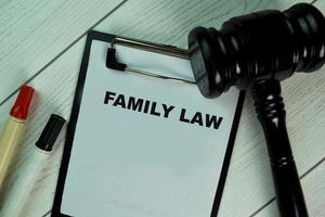 Derecho de familia escrito en el papeleo con martillo aislado sobre mesa de madera foto
