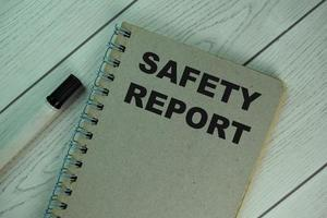 Bloc de notas de informe de seguridad aislado en la mesa de madera foto