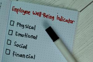 Employee wellbeing indicator written on a book with additional services isolated on wooden table
