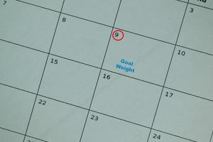 Goal weight on monthly calendar and marked 9th isolated on office desk