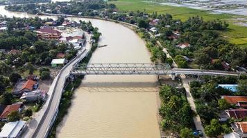 Bekasi, Indonesia 2021- Aerial drone view of a long bridge at the end of the river connecting two villages photo