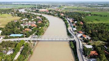 Bekasi, Indonesia 2021- Aerial drone view of a long bridge to the end of the river connecting  two villages photo
