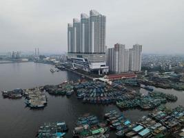 Jakarta, Indonesia 2021- Aerial drone view of Muara Angke beach with wooden boats leaning beside the pier photo