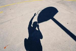 Man's shadow on the ground playing basketball