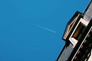Avión volando en el cielo azul en la ciudad de Bilbao, España foto