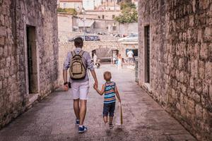 Father and son walking through the city and holding hands photo