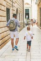 Father and son walking through old town street on summer vacation photo