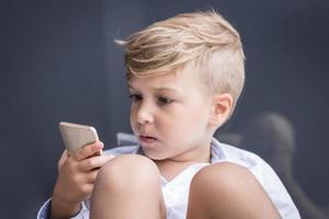Small kid watching something on smartphone photo