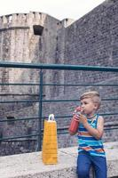 Little boy drinking water in the city photo