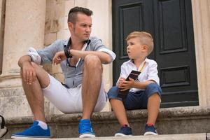 Father and son sitting on steps while relaxing in the city