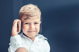 Portrait of happy boy talking on the phone photo