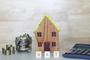 Model house with stack of coins money on wooden background photo