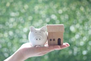 Selective focus of woman's hand holding piggy with model house on natural green background photo