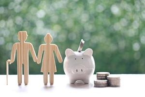 Couple cutout and piggy bank with stack of coins on natural green background