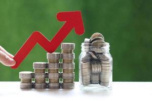 Mano de mujer sosteniendo el gráfico de flecha roja y pila de monedas dinero en botella de vidrio
