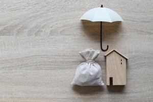 Casa modelo y sombrilla sobre fondo de madera foto