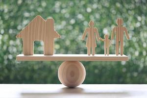 Casa modelo y modelo familiar en balancín de escala de madera con fondo verde natural