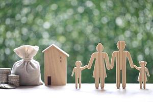 familia modelo y casa modelo con bolsa de dinero y pila de monedas