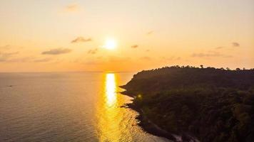 Aerial view of beautiful beach and sea with coconut palm tree at sunset time