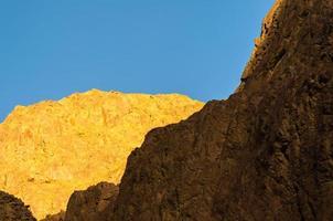 Sun shining on rock face photo