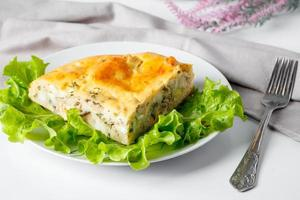 Homemade fish pie with greens on a plate photo