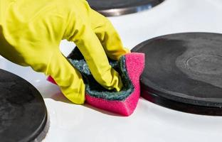 Person scrubbing a stove photo