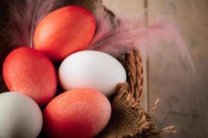 Huevos de Pascua blancos y naranjas sobre un fondo de madera foto