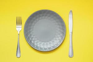 Empty gray plate and cutlery on yellow background