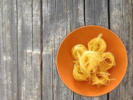 Pasta en un plato de naranja sobre un fondo de mesa de madera foto