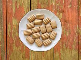 Striped cookies on a white plate on a wooden table background photo