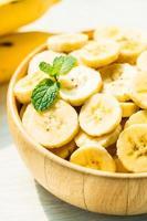 Rodajas de plátano amarillo crudo en un tazón de madera foto