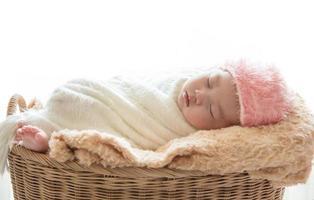 Newborn baby sleeping in a basket on white background photo