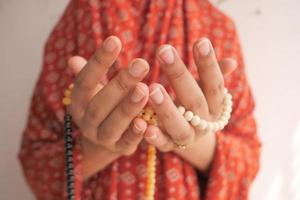 Close up of hands praying with beads photo