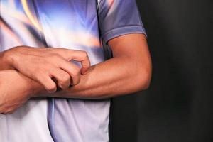 Man scratching forearm on black background photo
