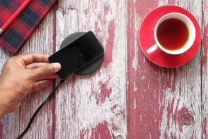 cargar un teléfono inteligente con almohadilla de carga inalámbrica foto