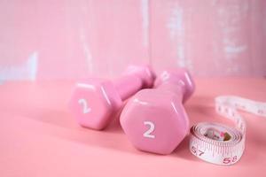 Pesas de dos libras sobre fondo rosa foto