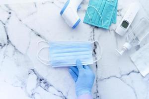 Mano en guantes médicos sosteniendo mascarillas quirúrgicas foto