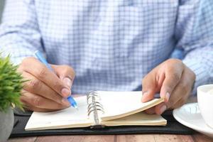 Cerca del hombre escribiendo en el bloc de notas