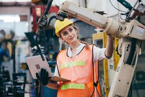 Woman inspecting machinery while holding a laptop photo