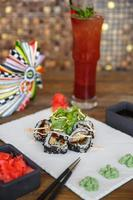 Sushi rolls topped with sesame side sauce photo