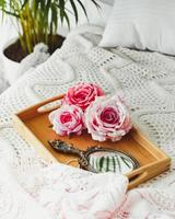Wood tray with mirror and pink roses put on knitted blanket