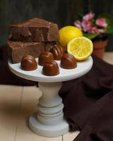 White small cake stand with milk chocolates and lemon on top