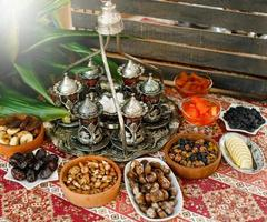 Traditional tea setup with antique tea tray and glasses and dry fruit bowls