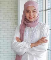 Beautiful Muslim Asian businesswoman stands smiling with happiness in office photo