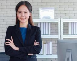 Beautiful young Asian businesswoman stands smiling with happiness in office