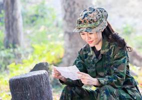 Retrato de una mujer soldado sentada felizmente leyendo una carta